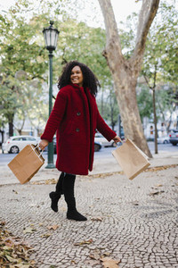 Portrait carefree young woman walking with shopping bags