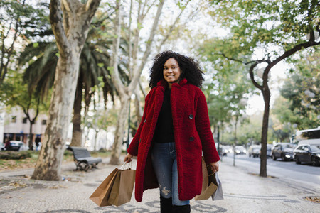 Portrait carefree young woman with shopping bags