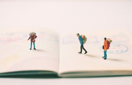 Miniature people figures with backpack walking and standing on p