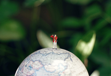 Miniature people photographer figures with camera standing on gl