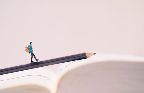 Miniature people figures with backpack walking on pencil and boo