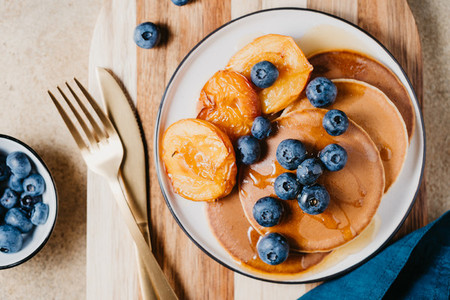 Top view of pancakes with grilled peaches fresh blueberry and maple syrup