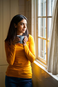 Persian woman drinking coffee while looking through the window