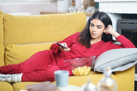 Persian woman at home watching TV and using remote control