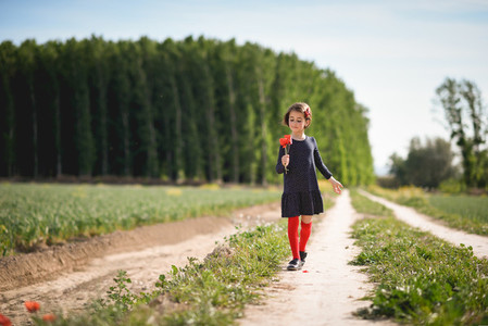 Little girl walking in nature field wearing beautiful dress