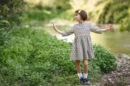 Little girl in nature stream wearing beautiful dress