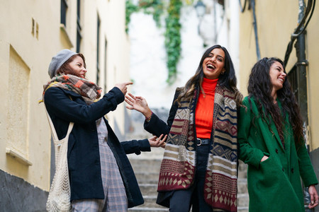 Multiethnic group of three happy woman walking together outdoors