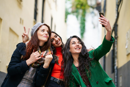 Group of three happy woman walking together outdoors