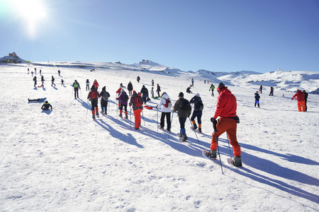 Group of people hiking with snowshoes at Sierra Nevada ski resort