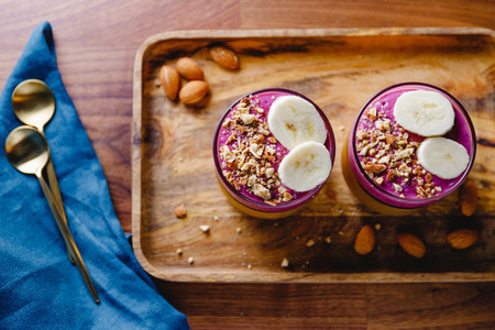 Top view of two glasses with violet berry and banana smoothie are served crushed almond on a wooden tray