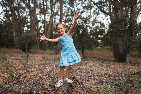 A girl plays swinging over a trunk in the forest