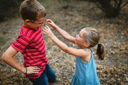 Two kids playing and dancing in the forest