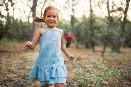 Two kids play running in the forest