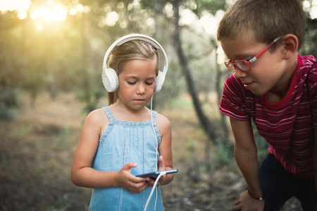 Two kids listening to music in the forest with headphones