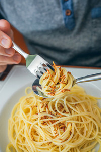 Hands of man eating spaghetti with worms