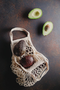 Avocado hass in a white eco net bag on a table