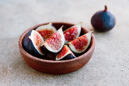 Ripe figs in a wooden small bowl on a table