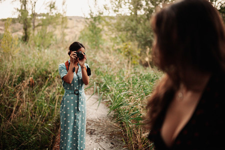 Two young women taking photos each other in the forest