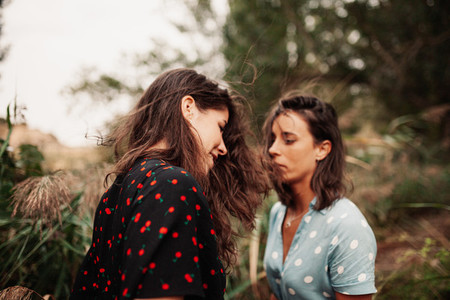 Two young women look at each other with wind in their hair