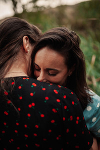 Two young women embraced on the field