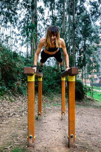 Athlete woman training on parallel bars