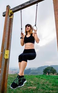 Female athlete doing gymnastic rings exercises