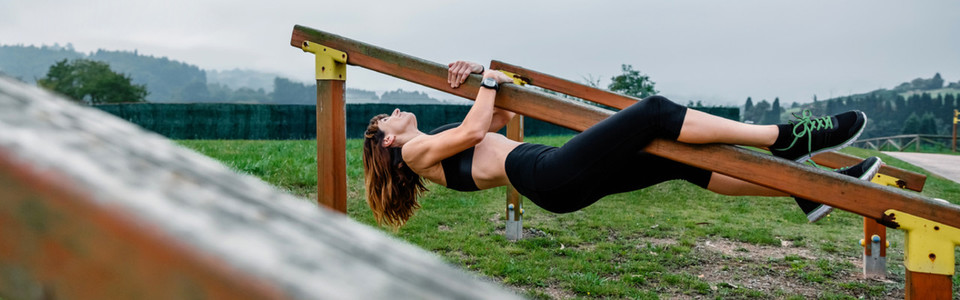 Sportswoman training hanging on a wooden bar