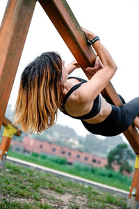 Sportswoman training hanging on a wooden bar