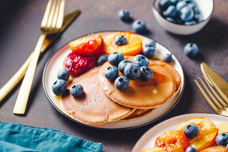Close up of pancakes with grilled peaches  fresh blueberry and maple syrup