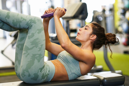 Young sportswoman on yoga mat doing situps in gym