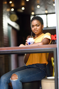 Smiling black woman with very short hair drinking a cocktail in an urban cafe