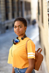 Young African woman wearing casual clothes and headphones looking at camera