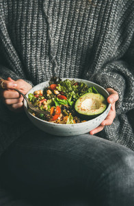 Woman in sweater eating healthy vegetarian dinner from Buddha bowl