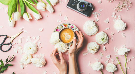 Female hands holding coffee  flowers and film camera  wide composition