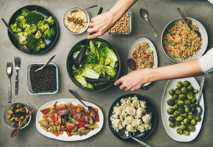 Healthy dishes in plates and woman hands taking fresh salad