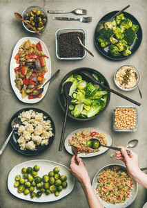 Healthy vegan dishes and woman hands taking couscous from plate