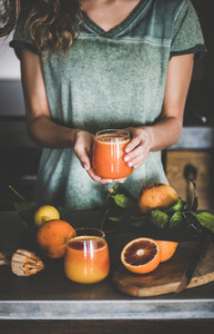 Woman holding glass of fresh blood orange juice or smoothie