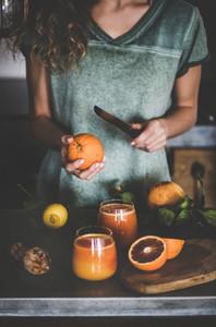 Woman making fresh blood orange juice or smoothie