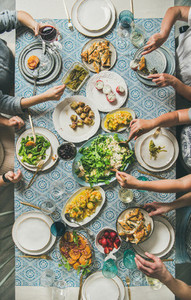 Mediterranean style dinner and human hands holding drinks and food