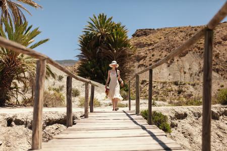Woman wearing dress walking on a wooden bridge in the desert