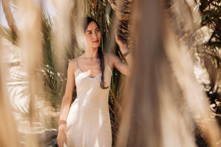 Woman wearing dress standing close to palm tree in the desert