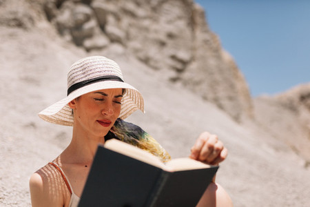 Woman reading a book wearing dress seating in the desert