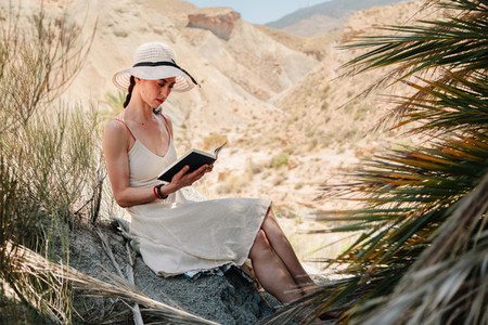 Woman reading a book wearing dress seating near to palm tree