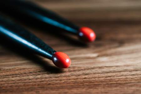 A pair of black drum sticks on a wooden table Close up view
