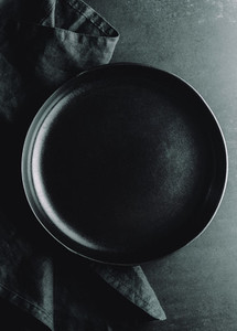 Top down view on an empty ceramic black plate on a dark background  Food or eating concept dark mockup