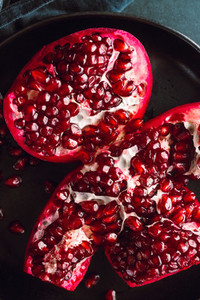 Top down view on a ripe pomegranate in a black plate on a dark background  Dark food photography