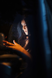 Young woman inside a car using her smartphone