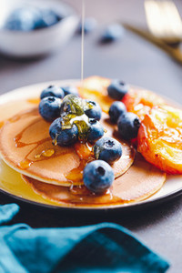 Pouring honey on pancakes with grilled peaches and fresh blueberry