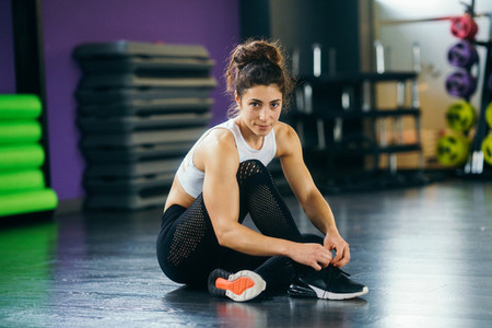 Athletic woman tying her sneakers at the gym