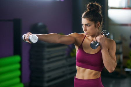 Sporty woman punching and boxing with dumbbells